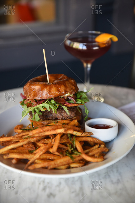 Gourmet burger and fries on a plate with a cocktail