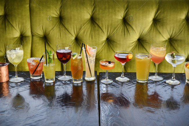 Row of cocktails lined up on a table in front of a green booth