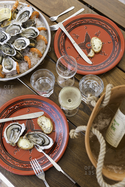 Monte Carlo, Monaco - September 20, 2016: Seafood, red plates and wine on a wooden table
