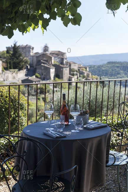 Gordes, France - October 19, 2016: Cafe table overlooking a stone village on a hillside
