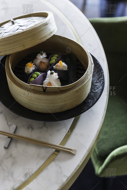 Dumplings with roe and edamame in a bamboo steamer on a table