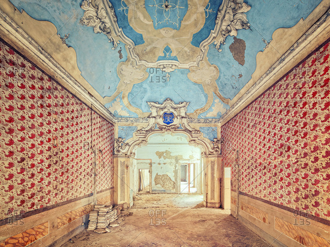 Room in an abandoned mansion with peeling wallpaper and ornate ceilings