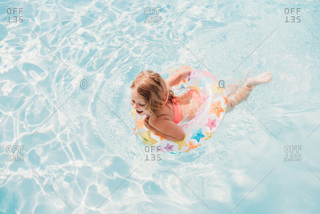 Little girl swimming in pool with star floatation ring