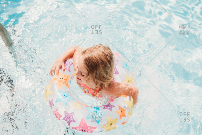 Young girl swimming in pool with star floatation ring
