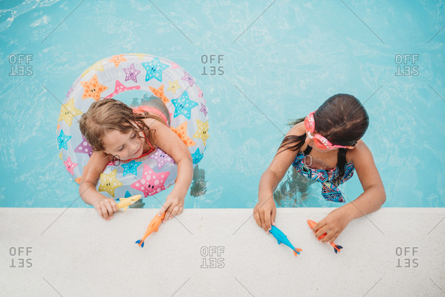 Two girls in a swimming pool with water toys