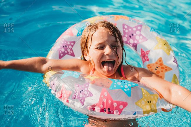 Little girl swimming in pool with star floatation ring sticking her tongue out