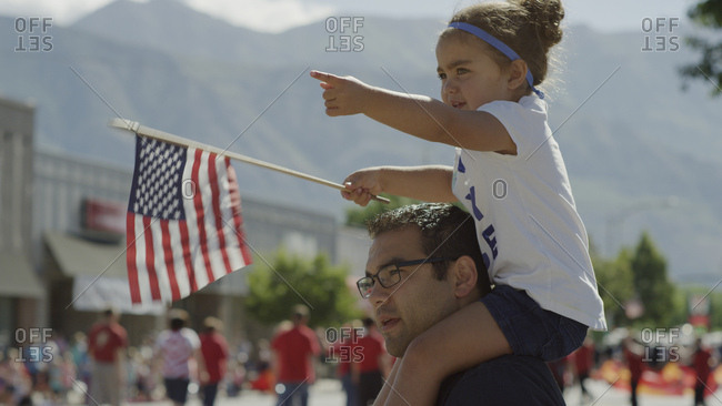 Patriotic father carrying daughter on shoulder and waving American flag at parade