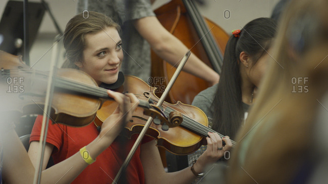 Selective focus view of serious teenage girl musician playing violin in band class