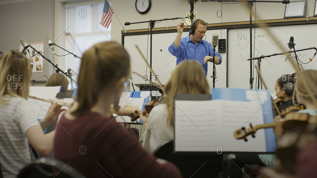 Selective focus view of teacher conducting musicians in band class