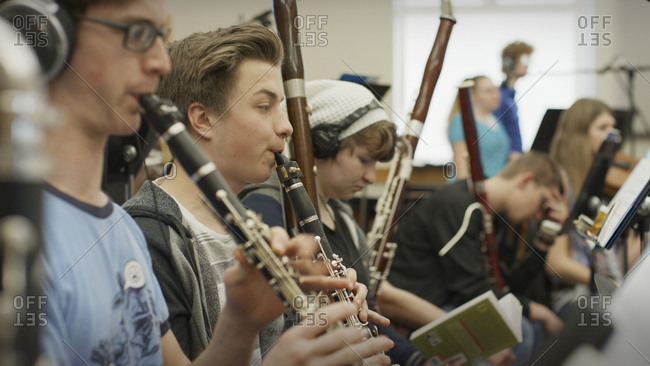 Selective focus view of serious teenage boy musician playing clarinet in band class