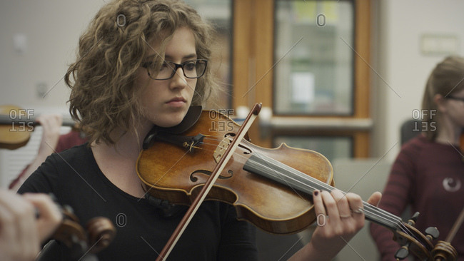 Serious teenage girl musician playing violin in band class