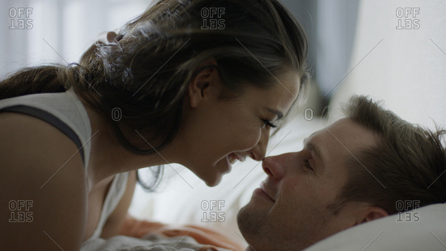 Close up profile of smiling happy couple touching noses on bed