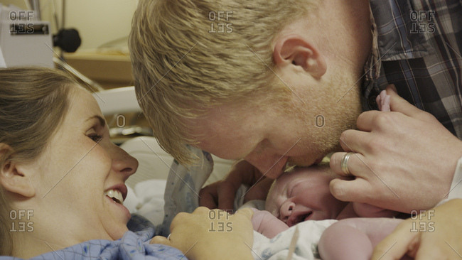 Profile view of new mother and father admiring newborn baby in hospital