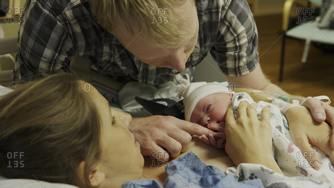 High angle view of new mother and father admiring newborn baby in hospital