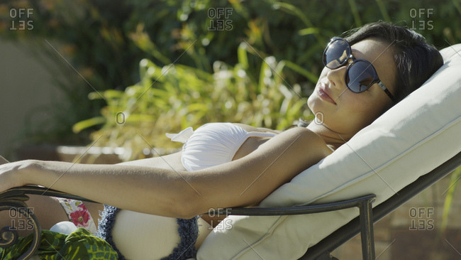 Profile view of woman in sunglasses and bikini sunbathing and laying on lawn chair