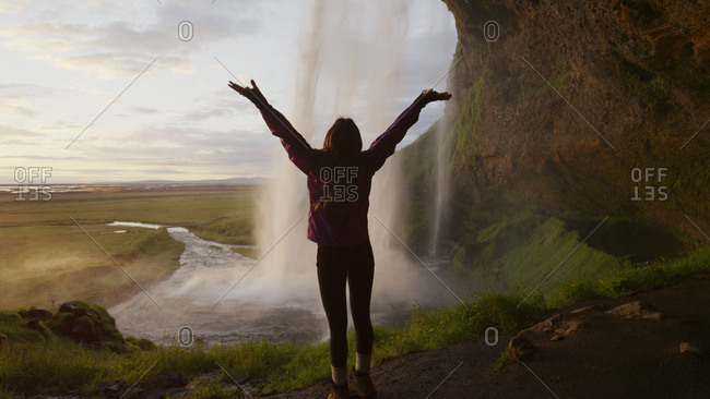 Rear view silhouette of woman with outstretched arms standing behind waterfall overlooking remote landscape