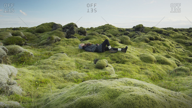 Side view of woman laying in mossy field in remote rocky landscape under clear blue sky
