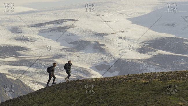 High angle view of hikers walking on grassy hilltop over snowy remote landscape