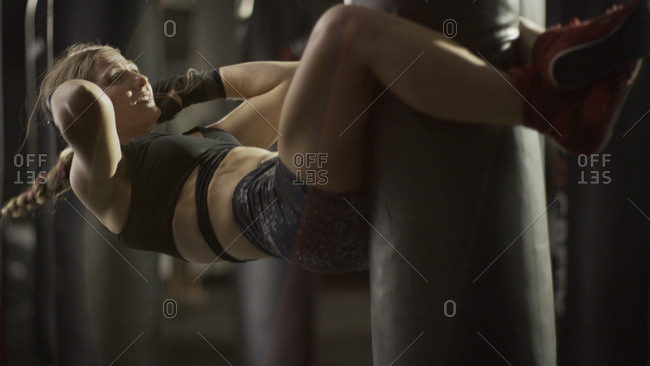 Selective focus view of female boxer working out and doing sit-ups on punching bag in gym
