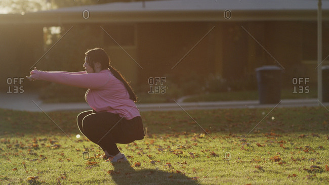 Profile of backlit woman squatting and working out in sunny backyard