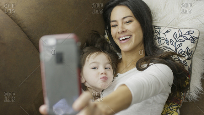 High angle selective focus view of playful mother and daughter posing and taking selfie with smartphone on sofa