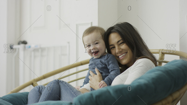 Low angle selective focus portrait of mother and baby son posing and sitting in chair