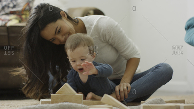 Mother and curious baby son sitting on floor and playing with building blocks