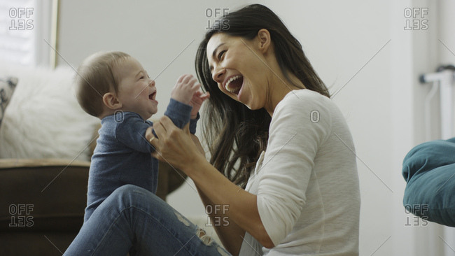Profile of blurred mother and curious baby son sitting on floor and playing