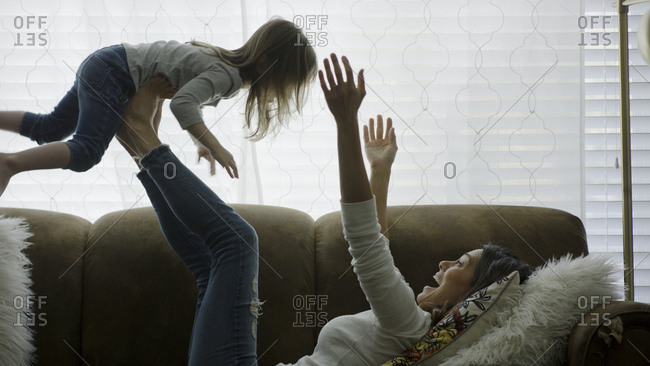 Profile of laughing playful mother lifting daughter in mid-air and playing on sofa