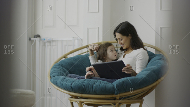 Selective focus view of mother and daughter using digital tablet and sitting in chair