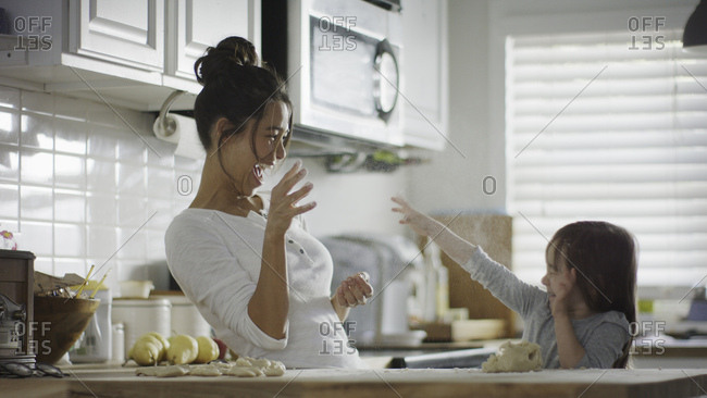 Playful mother and daughter baking and tossing dough in kitchen