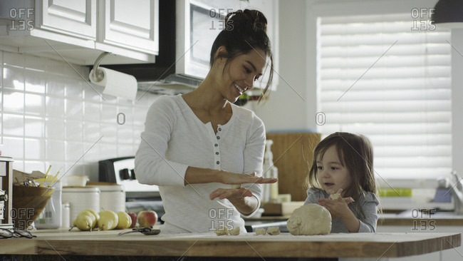 Smiling mother teaching daughter to bake and roll dough in kitchen