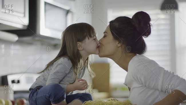 Profile of playful mother and daughter kissing over spaghetti pasta in kitchen