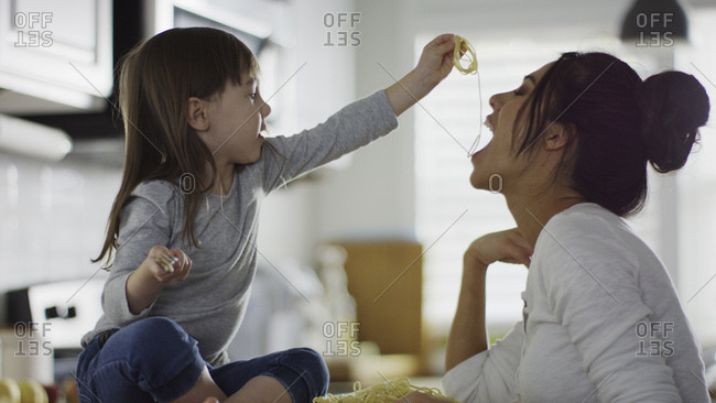 Profile of playful daughter feeding mother spaghetti pasta in kitchen