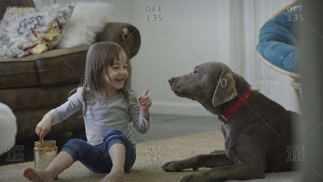 Naughty girl feeding pet dog peanut butter on living room floor