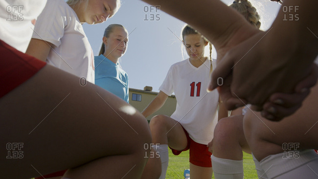 Selective focus view of serious soccer team players holding hands in huddle before game