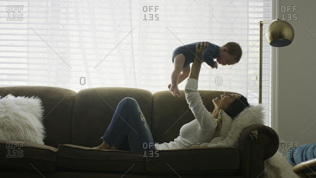 Profile of laughing playful mother baby son in mid-air and playing on sofa