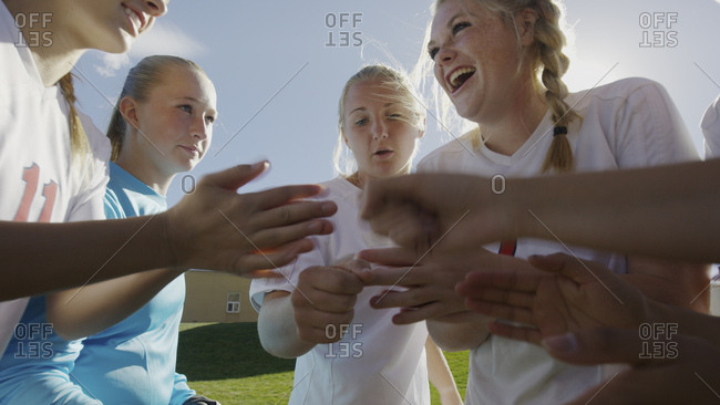 Low angle blurred view of soccer team players cheering in huddle before game under clear blue sky