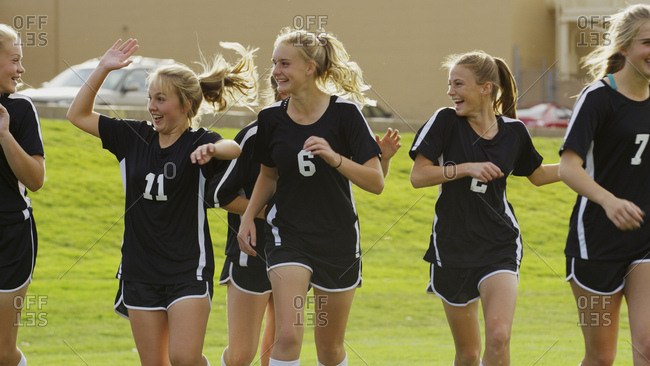 Proud athlete with soccer teammates cheering after game victory on field