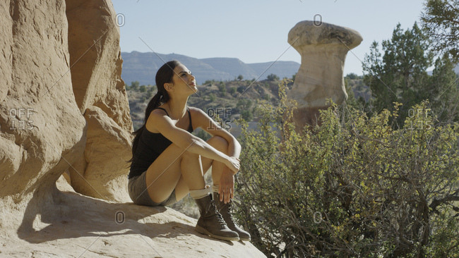 Smiling climber sitting on rocky cliff admiring scenic view of rock formations and trees in remote desert landscape