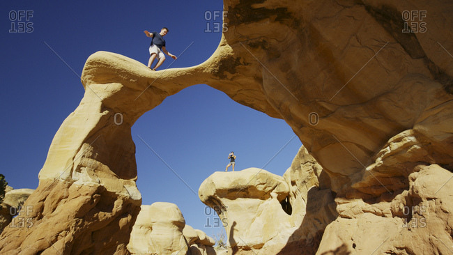 Low angle view of climbers balancing on scenic rock formations under clear blue sky