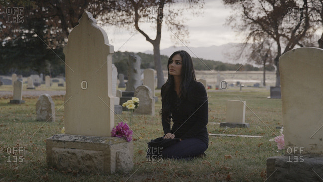 Sad pensive woman sitting at grave in lonely cemetery