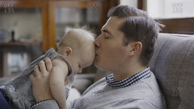 Close up profile of father kissing baby daughter's hair on sofa