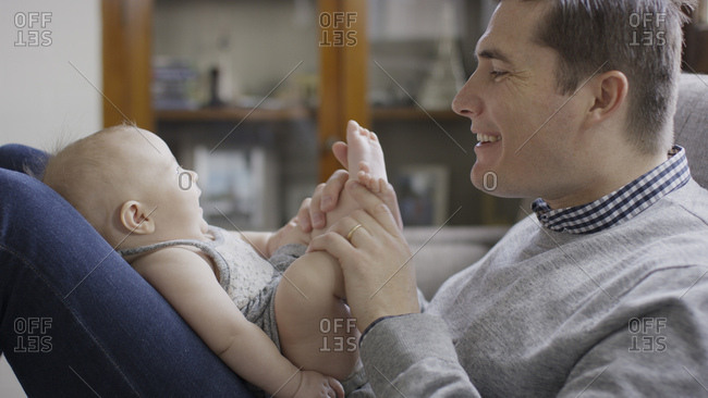 Close up profile of smiling father playing with baby daughter's feet on sofa
