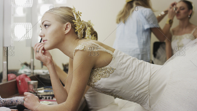 Profile of serious ballet dancer in costume applying makeup backstage before show
