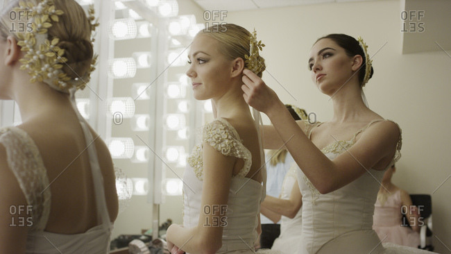 Serious ballet dancers in costume styling hair backstage before show