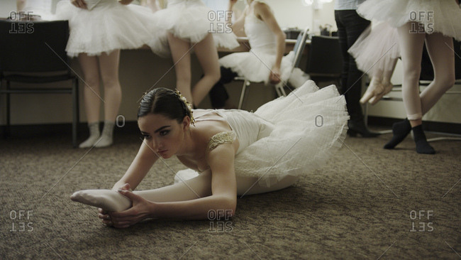 Serious ballet dancer in costume stretching backstage before show
