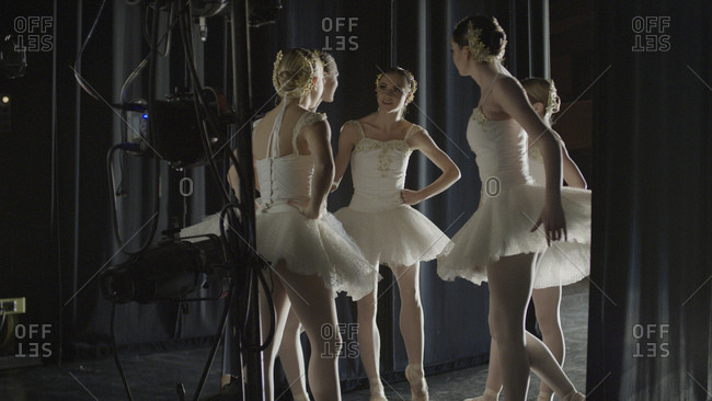 Serious ballet dancers in costume standing backstage during show