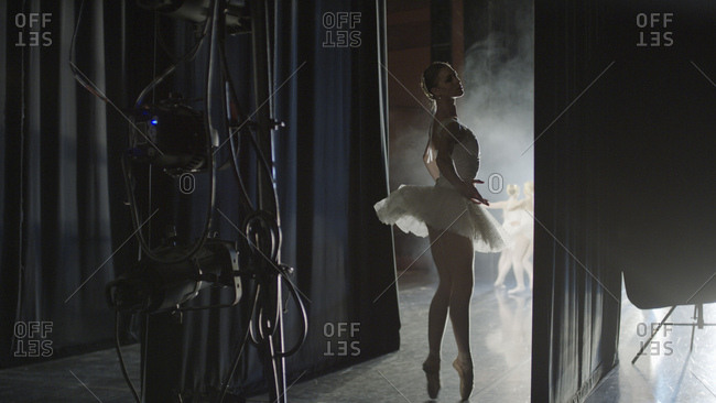 Silhouette of serious ballet dancer in costume ready to dance onstage during show