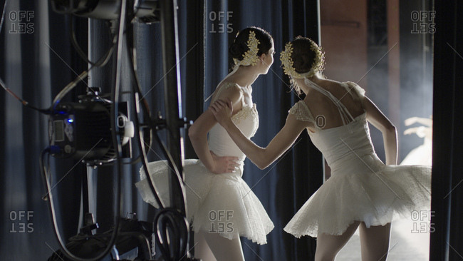 Serious ballet dancers in costume watching performance backstage during show
